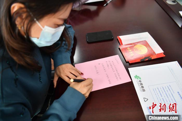 在长春市二道区荣光街道办事处,工作人员在给远方的家人写信。 张瑶 摄